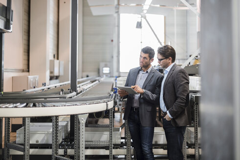 Two businessmen with tablet talking at conveyor belt in factory - DIGF03734