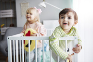 Portrait of smiling toddler standing in crib with his sister in the background - ABIF00259