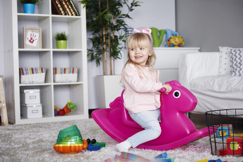 Portrait of smiling little girl sitting on pink rocking horse in the living room - ABIF00265