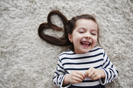 Portrait of laughing little girl lying on carpet - ABIF00271
