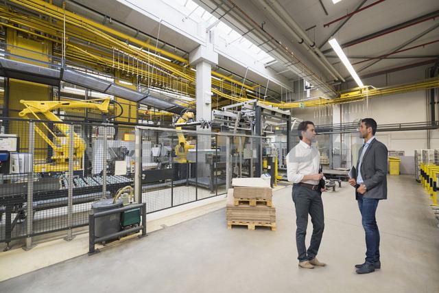 Two businessmen talking on factory shop floor - DIGF03751 - Daniel Ingold/Westend61
