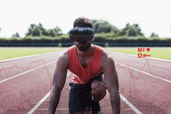 Athlete in starting position on tartan track wearing VR glasses surrounded by data - UUF13256