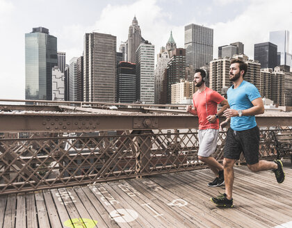 USA, New York City, two men running on Brooklyn Brige with data on the ground - UUF13259