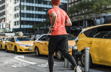 USA, New York City, man running in the city with data on pavement - UUF13262