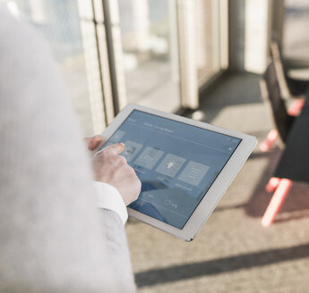 Woman using tablet with smart home control functions in office - UUF13265