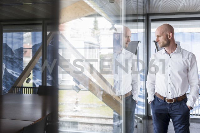 Businessman standing in office thinking - DIGF03759