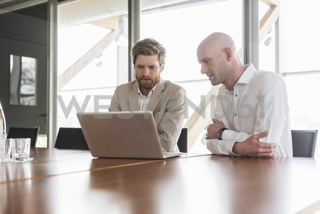 Two businessmen sharing laptop in conference room - DIGF03762 - Daniel Ingold/Westend61