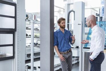 Two men talking in modern factory - DIGF03792