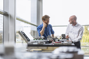 Two smiling men working on product in company - DIGF03795