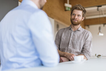 Two businessmen talking in break room - DIGF03804