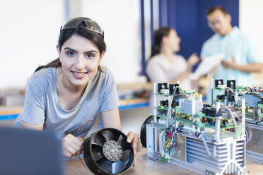 Portrait of smiling woman working on computer equipment - ZEF15280