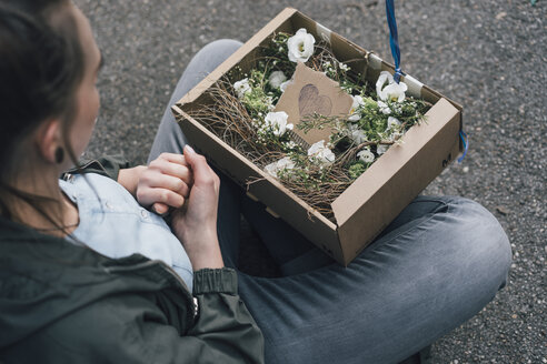 Woman with floral arrangement in cardboard box sitting on the ground - GUSF00605