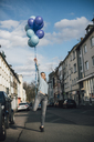 Smiling woman with blue balloons on the street - GUSF00608