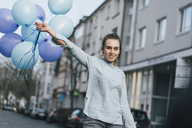Portrait of smiling woman with blue balloons on the street - GUSF00620