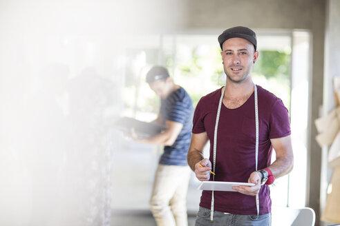 Portrait of smiling fashion designer holding tablet in studio - ZEF15304