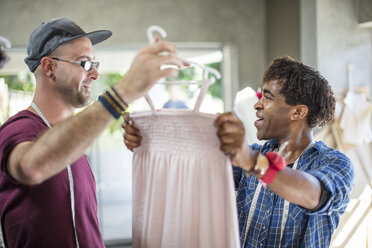 Smiling fashion designer showing dress to colleague - ZEF15310