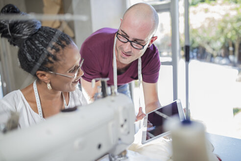 Fashion designer showing tablet to seamstress in studio - ZEF15328
