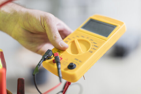 Close-up of electrician holding voltmeter - ZEF15346