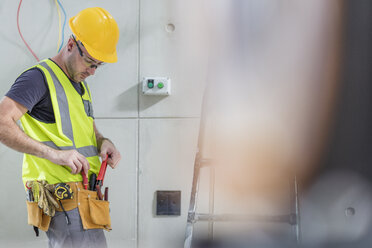 Electrician taking tools out of belt on construction site - ZEF15349