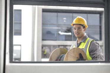 Portrait of construction worker carrying cable drum - ZEF15355