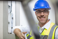 Portrait of smiling electrician at fuse box - ZEF15358