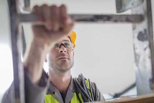 Close-up of construction worker climbing ladder - ZEF15361
