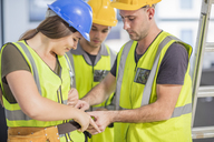 Construction worker helping colleague with tool belt - ZEF15370