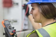 Young female electrician working with voltmeter at fusebox - ZEF15373