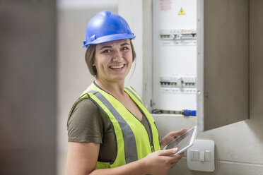 Portrait of smiling female electrician with tablet at fusebox - ZEF15376