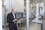 Businessman looking at machine in modern factory - DIGF03829