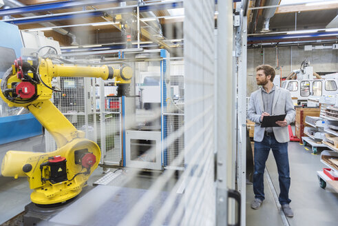 Businessman looking at industrial robot in modern factory - DIGF03832