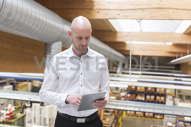 Businessman using tablet in modern factory - DIGF03841