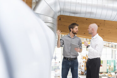 Two businessmen with tablet talking at pipework in factory - DIGF03847