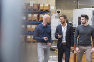 Three men walking and talking in factory storeroom - DIGF03850