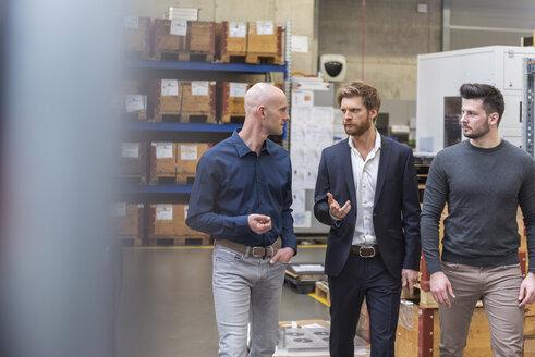 Three men walking and talking in factory storeroom - DIGF03850