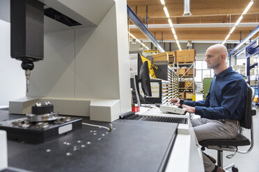 Man using computer at machine in modern factory - DIGF03865