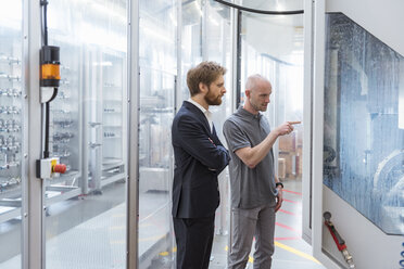 Businessman and employee talking at machine in modern factory - DIGF03868