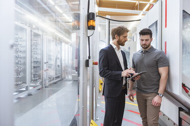 Two men with tablet talking at machine in modern factory - DIGF03871