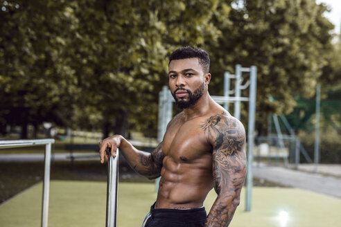 Portrait of tattooed physical athlete  on sports field - DAWF00590
