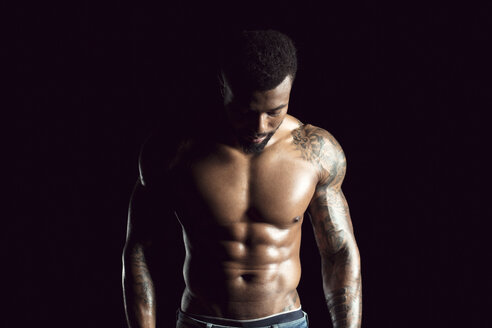 Tattooed physical athlete in front of black background - DAWF00605