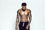 Tattooed physical athlete in front of light background - DAWF00611