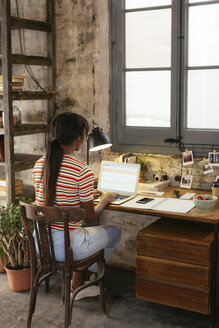 Back view of young woman sitting at desk in a loft working on laptop - EBSF02282