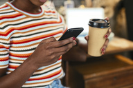 Woman holding coffee to go while using smartphone, close-up - EBSF02288