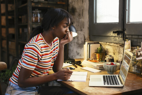 Pensive young woman sitting at desk in a loft looking at laptop - EBSF02291