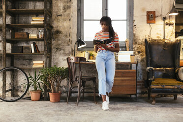 Young woman standing in front of desk in a loft using notebook - EBSF02294