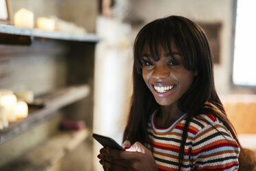 Portrait of happy young woman with cell phone - EBSF02306