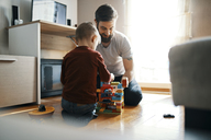 Father and son sitting on the floor at home playing together with building bricks - ZEDF01277