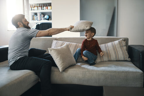 Father and little son playing together on the couch in the living room - ZEDF01289