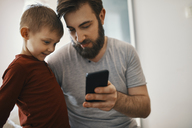 Father explaining little son smartphone - ZEDF01292