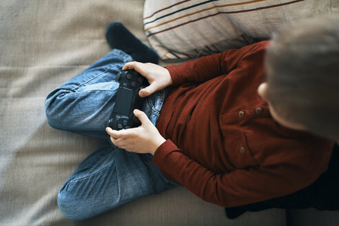 Little boy sitting on the couch playing computer game, top view - ZEDF01298